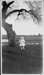 A little girl stands under a tree in her white sunday dress and hat. She has her hands on her hips and seems to be posing with a preternatural self-satisfaction.