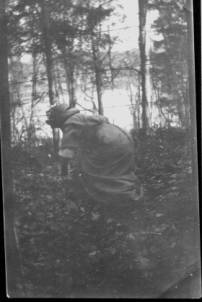 A woman in Victorian dress crawls through the leaves under a barbed wire fence. She is in a scrub-forest. There is a lake in the background. Her face is obscured by shadows. No skin shows. She is hiding, escaping, vanishing into the forest.
