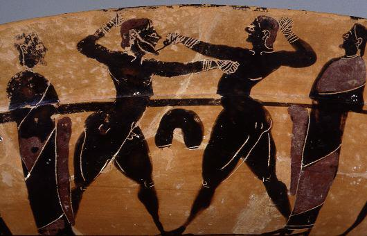 A red terracotta Greek bowl showing a bearded man defeating a clean shaven man in a boxing match. Their fists are wrapped in cloth, but otherwise they stand naked.  Their penises are small indeed.  Ha Ha Ha.